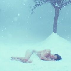 Elizabeth Dimitrov laying motionless in the snow  near a tree bare of any leaves