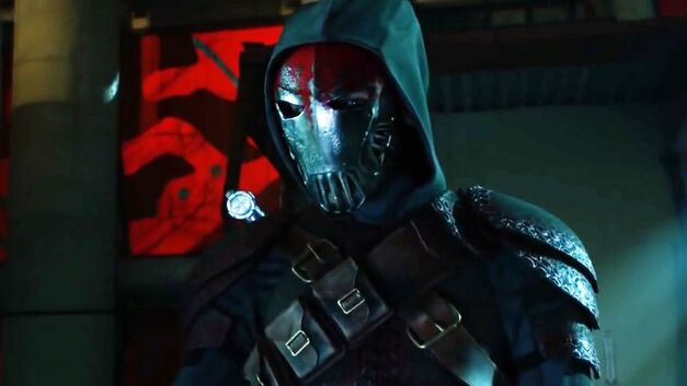 Azrael is seen in an iron mask, and dark cape and hood. He is wearing an ammunition belt that stretches across his chest like an X.