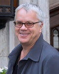 Tim Robbins—a white male with close-cut gray hair, light-colored eyes, smiling and wearing narrow, plastic-framed eyeglasses and a dark gray jacket over a black shirt—attending the Toronto International Film Festival in September 2012 at age 53.