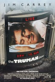 """Film poster showing a large skyscraper located next to several smaller ones. On the side of the building is a large screen, showing a man laying his head on a pillow, eyes closed and smiling. Digital text above and below the screen state """"LIVE"""" and """"DAY 10,909"""", with the film's title right below it. Text at the top of the image includes the sole starring credit and text at the bottom includes the film's tagline and credits."""