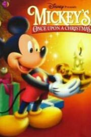 A short anthropomorphic male mouse standing at the left side of the image is holding a candle holder with a brightly burning candle, positioned on the right side of the image, with both of his hands. The mouse is wearing red shorts with white buttons and yellow shoes and is happily smiling. In the background on the left side of the picture stands a decorated Christmas tree with colorfully wrapped gifts lying under it. The poster includes the film and company's title.