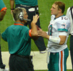 Candid photograph of Lee wearing a green polo shirt and headset standing on a football sideline and gesturing with his right hand in a conversation with Chad Pennington who is wearing a Miami Dolphins uniform