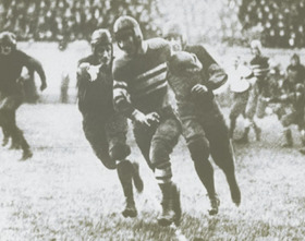 McMillin with the football, pursued by other players
