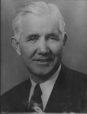 Portrait of a smiling McMillin in a suit
