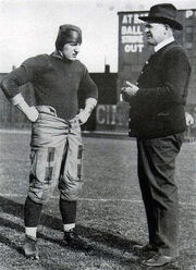 A coach conversing with a football player