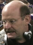 The head of a bald man wearing glasses. He has a mustache and a headset around his neck.