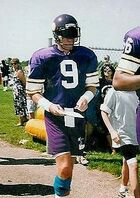 "A white man wearing a purple jersey with white trim and a large numeral ""9"" in white on his chest. He is wearing a purple American football helmet with a dark visor covering his eyes."