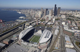 The stadium from the air on a clear day. SEAHAWKS STADIUM is painted on the white partial roof. The stadium is surrounded by roads and buildings.