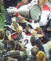 A player in a white uniform with red trim and a black number 2 on his chest raises a large silver trophy over his head.