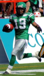 man in green Canadian football uniform runs with a football on a football field