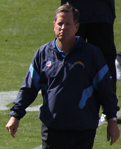Candid waist-up photograph of Turner walking on a football field wearing a dark blue San Diego Chargers jacket