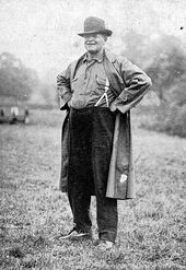 A smiling old man in glasses and overalls, hands on hips