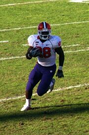 Football player in #28 white uniform with blue pants and red helmet runs with the football