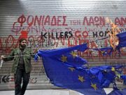 Greece-man-burning-flag-in-front-of-graffiti