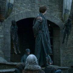 Theon pokazuje dwa dziecięce ciała.