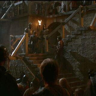 Podrick observa como Tyrion faz um discurso para os defensores de <a href=