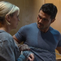 Nathan tries to unlock Maxie's cuff with a paperclip but they stare at each other instead
