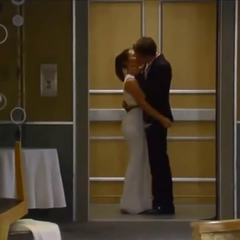 Michael and Kiki kissing in an elevator