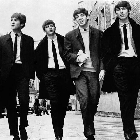 The Beatles walking down a street.