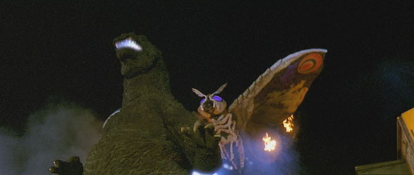File:Mothra approaching Godzilla's back.jpg