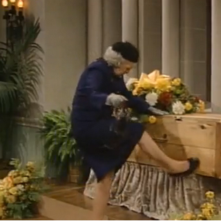 The woman, kicking Mrs. Claxton's coffin.