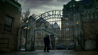 Jim waiting outside the Arkham Asylum gate