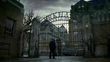 Jim waiting outside the Arkham Asylum gate