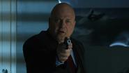 Nathaniel Barnes pointing a gun at Jim Gordon