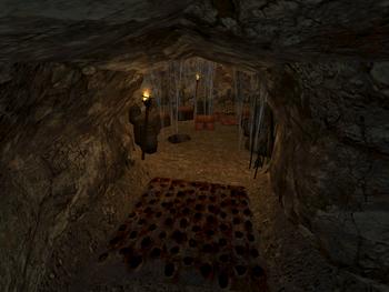 Jaskinia prowadząca do skarbca na końcu z pułapką po drodze. W tle widać beczki i kufry