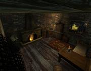 Przekrojowy rzut na wnętrze pracowni, w którym znajduje się alchemik stojący przy stole. Od lewej: pulpit z książką, kominek, stół alchemiczny, szafa, kufer i łóżko