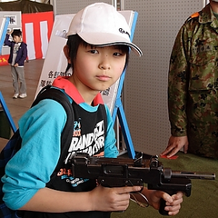 A Japanese School boy holding the PM-9, a good example of how the gun is held from the hip; the weapon's magazine has been removed to prevent accidental firing.