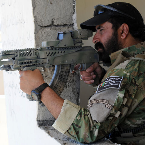 An Afghan National Police Officer aiming his AMD-65.