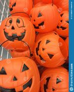 Plastic-halloween-pumpkins-display-white-wire-basket-full-jack-o-lanterns-used-children-to-gather-candy-127728620