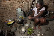 A-young-woman-cooks-in-her-kitchen-in-mirebalais-bj2b4g