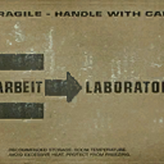 The Arbeit Laboratories logo on a cardboard crate texture.