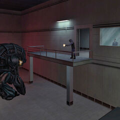 The G-Man spotted across the room while a security guard fires at a Gargantua at the end of <i>Uplink</i>.
