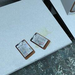 Dos portapapeles en una oficina de Laboratorios Aperture, incluyendo uno sobre el Reemplazo de Rodilla Avanzado.