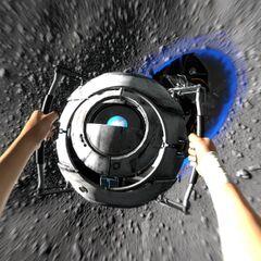 Chell agarrándose a Wheatley siendo absorbidos por el vacío en la luna
