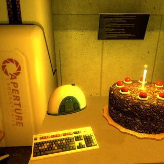 El pastel, una radio y el teléfono rojo de Aperture Science sobre una mesa de la cámara de <a href=