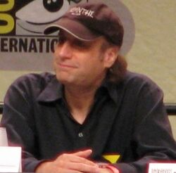 A seated man wearing a cap smiles as he looks into the distance. His hands are crossed.