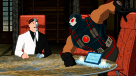 """Two-Face, a scarred man in a dress suit, sits at an executive chair while Bane, a large muscular man in a costume, tries to sit in another executive chair that is labelled """"In memoriam of Mr. Freeze"""""""