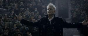 Grindelwald wita się ze zgromadzonymi rozkładając ręce, w tle jest siedząca na trybunach widownia