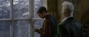Credence patrzy na różdżkę, którą dostał od stojącego za nim Grindelwalda