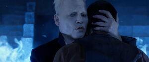 Grindelwald tulący Credence'a do swojego ciała, jedną ręką trzyma go za tył głowy