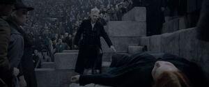 Grindelwald stoi nad ciałem martwej, rudowłosej czarownicy. Po bokach i w tle stoi zszokowana jej śmiercią widownia