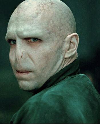 Odwracający się łysy i beznosy Lord Voldemort w sinozielonych szatach