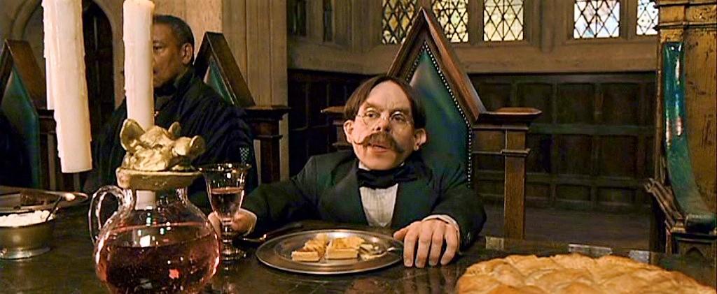Profesor Kratiknot sedící na zeleně polstrované židli s rukama na stole, v jedné drží pohár s nápojem.