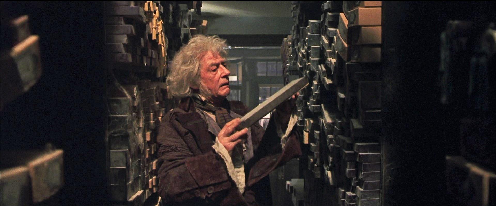 Ollivander hledí na právě vytaženou krabici s hůlkou, kterou předtím vytáhl z police.