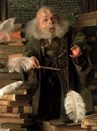 Profesor s pozdviženou hůlkou a vznášejícím se bílým pírkem.