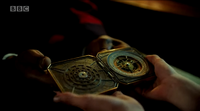 Lyra holding the alethiometer